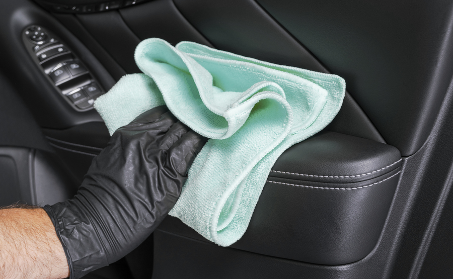 A man cleaning car seat with blue microfiber cloth. Car detailing or valeting concept. Selective focus. Car detailing. Cleaning with sponge. Worker cleaning. Car wash concept solution to clean